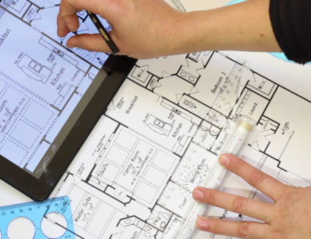 the-house-plan-on-tablet-screen-and-on-paper-an-architect-using-a-drawing-tools-and-looking-at-a-house-plan-on-tablet-touch-screen_bsjwn4_xe_thumbnail-full01